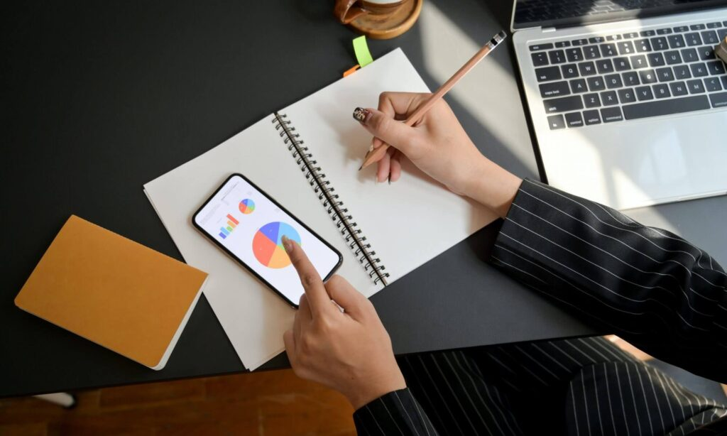 Moça fazendo anotações e checando dados no smartphone enquanto pensa em novas estratégias de copywriting