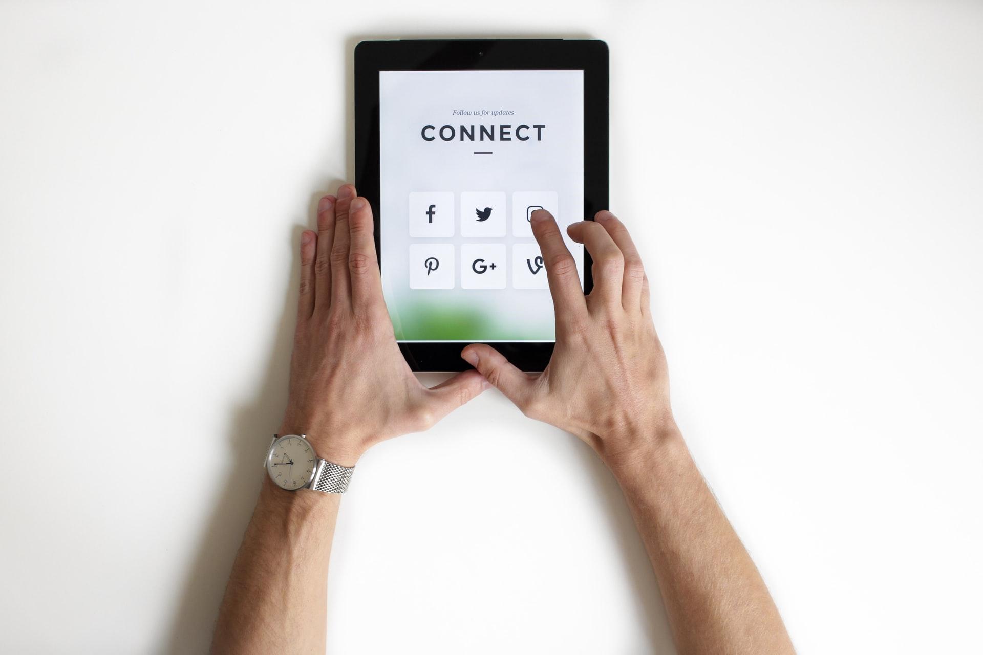 vídeo marketing: duas mãos masculinas interagindo com um tablet conectado às redes sociais