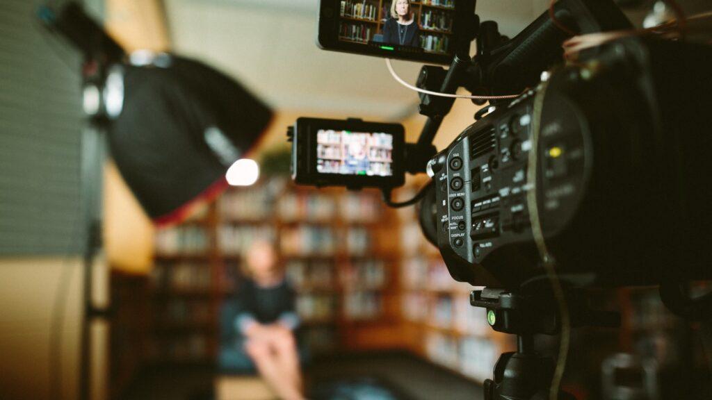 filmadora profissional apontada para entrevistada sentada ao fundo