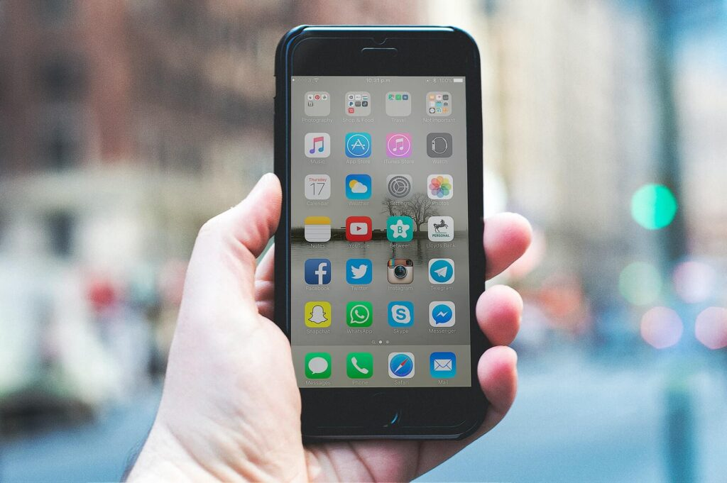 mão segurando smartphone na tela inicial onde ficam as redes sociais mais usadas