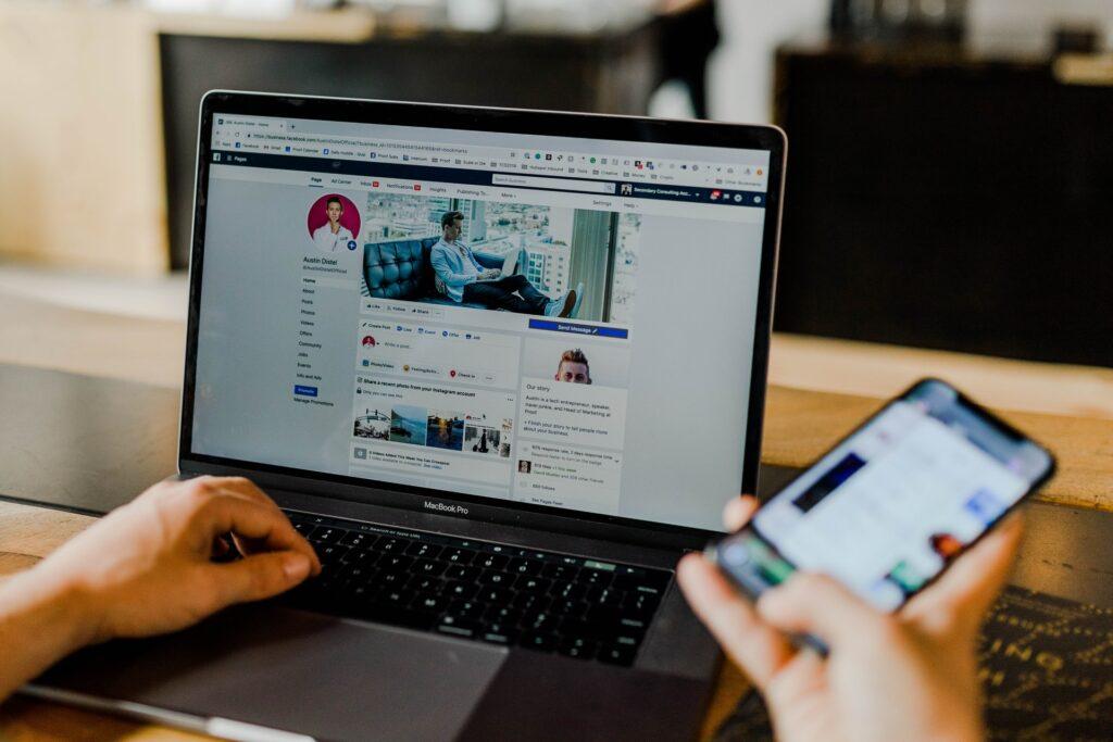 profissional conferindo suas redes sociais no notebook e no smartphone para identificar tendências de tráfego para Vídeos marketing