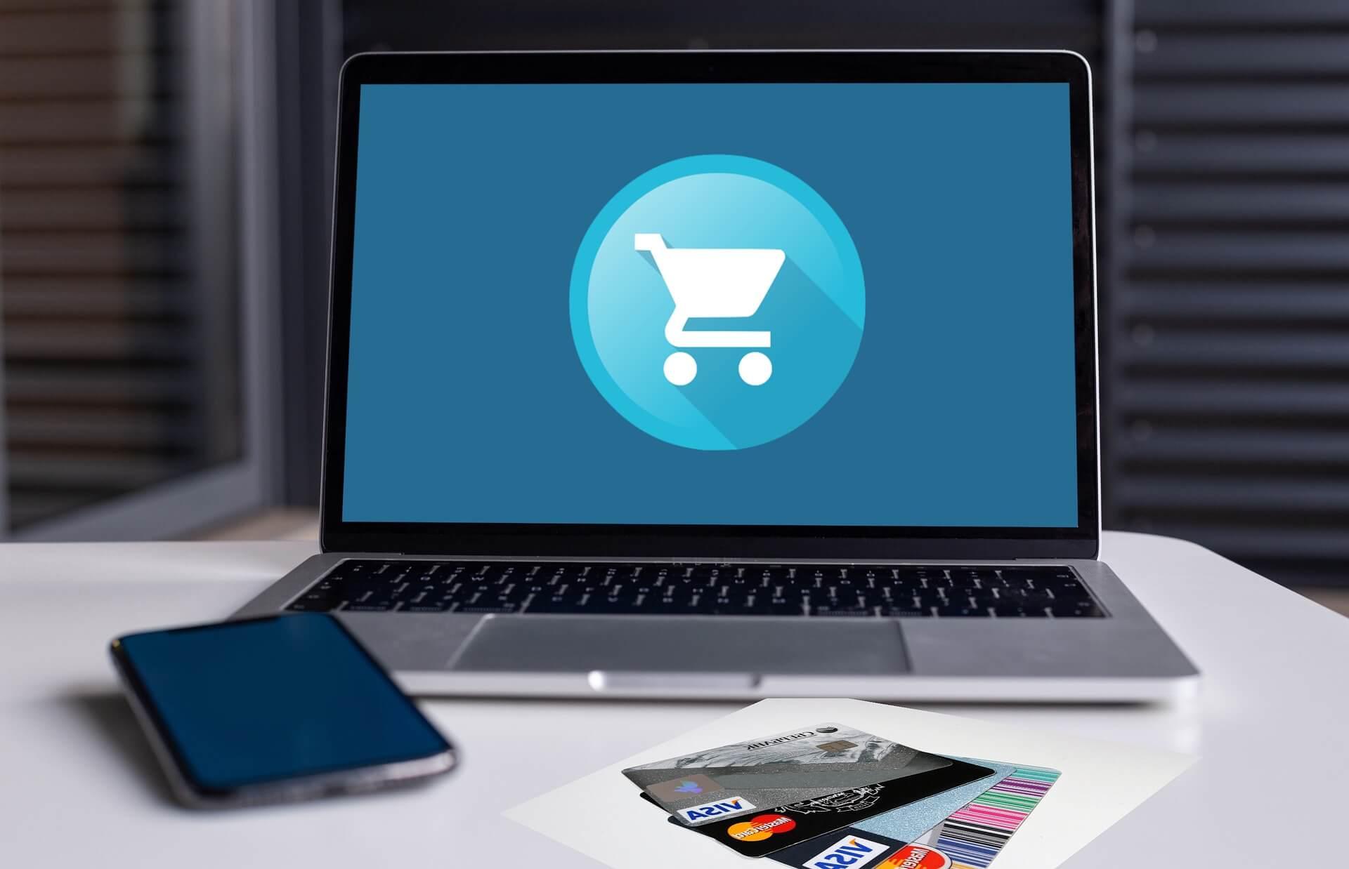 Imagem de um carrinho de compras na tela de um notebook ao lado de alguns cartões de crédito e um smartphone.